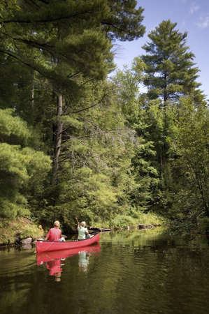 Muskokas, Ontario, Canada; couple canoeing down a river photo