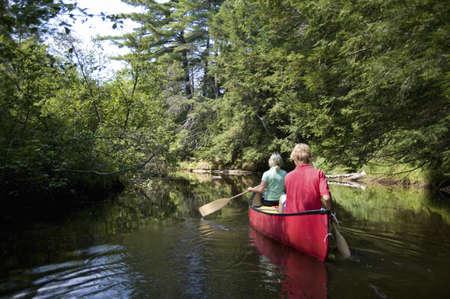 Muskokas, Ontario, Canada; couple canoeing down a river photo