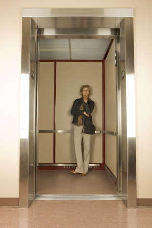 go inside: Woman in an elevator Stock Photo