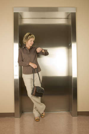 go inside: Woman waiting for an elevator Stock Photo