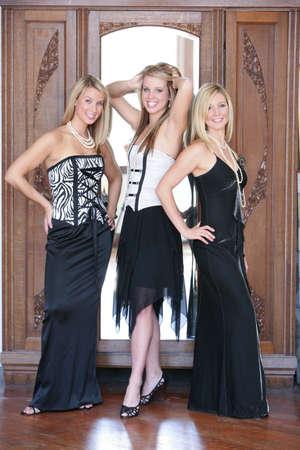 Three teenage girls dressed in formal wear photo
