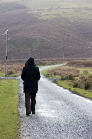 caucasian ancestry: Person walking down rural road,  Northumberland, England