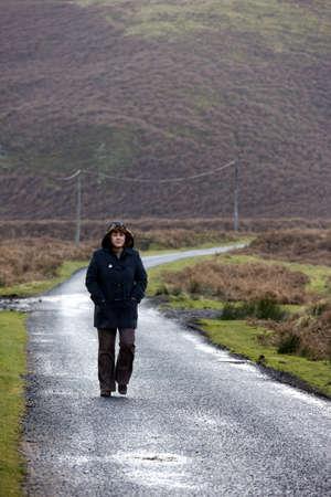 caucasian ancestry: Woman walking down rural road,  Northumberland, England Stock Photo