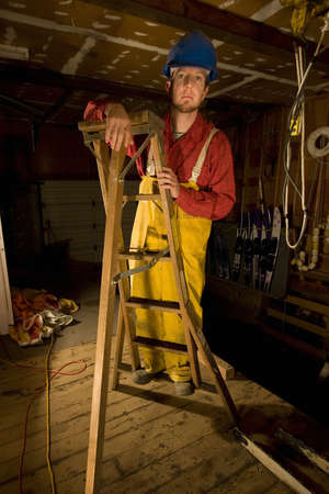 waders: Man in hip waders climbing a ladder