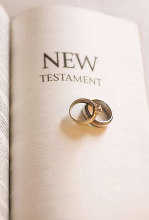 belief system: Holy matrimony; New Testament and wedding rings Stock Photo