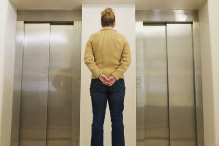 caucasian ancestry: Woman waiting for an elevator Stock Photo