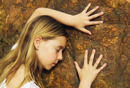 compassionate: Child touching a rock Stock Photo