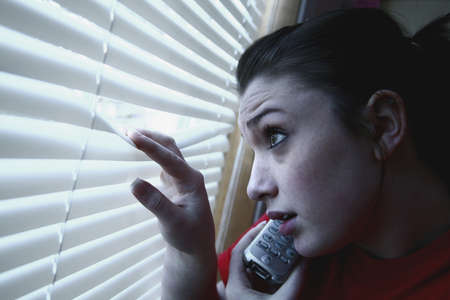 Teenage girl on the phone, looking out the window photo