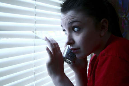 terrorized: Teenage girl on the phone, peeking out the window