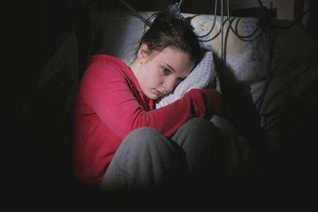 paranoia: Adolescente spaventata, seduta in camera da letto  Archivio Fotografico