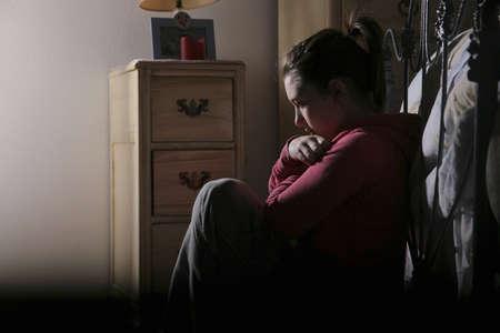 10 代の少女が彼女のベッドのフィートで座っています。
