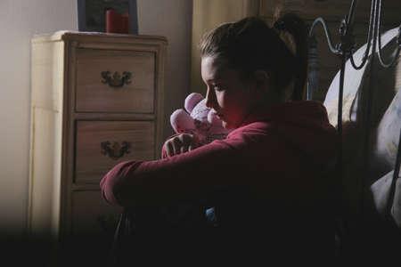 alarming: Adolescente sentado en la sala con el oso de peluche  Foto de archivo