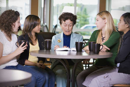 caucasian ancestry: Group of girls listening to senior woman in restaurant