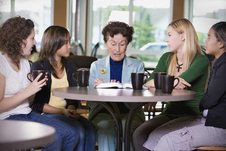 80s adult: Grupo de ni�as escuchando a mujer senior en restaurante  Foto de archivo