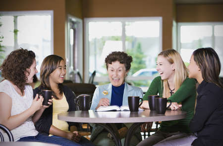 preadolescent: Group of girls listening to senior woman in restaurant