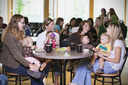 grote groep mensen: Groep van jonge moeders ontspannen in cafe