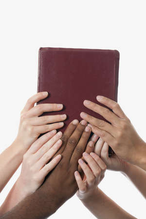 medium shot: Interracial hands holding up a bible Stock Photo