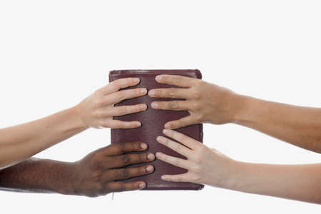 caucasian ancestry: Interracial hands holding up a bible Stock Photo