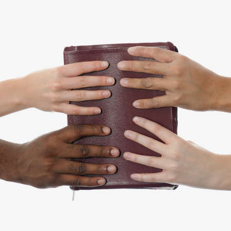 Interracial hands holding up a bible Foto de archivo