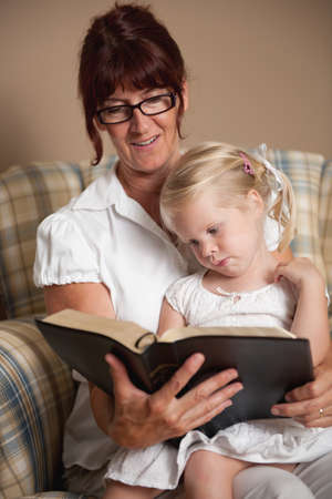 reading room: A grandmother reading the bible to her granddaughter