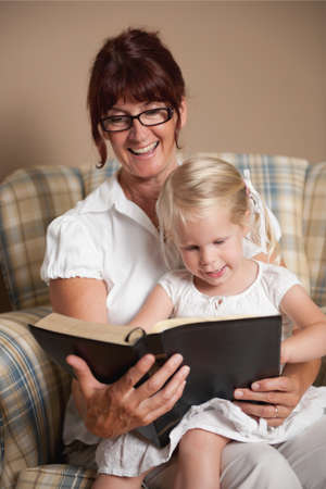 A grandmother reading the bible to her granddaughter photo