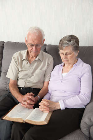 caucasian ancestry: An elderly couple having worship with the Bible