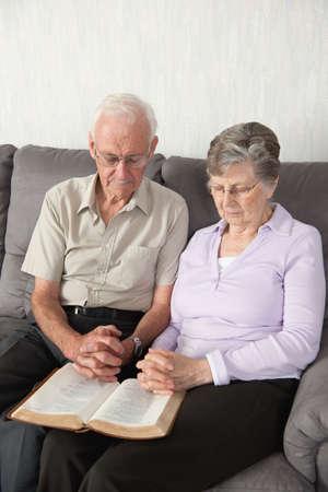 80s adult: Una pareja de ancianos que habiendo culto con la Biblia