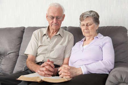 personas orando: Una pareja de ancianos que habiendo culto con la Biblia
