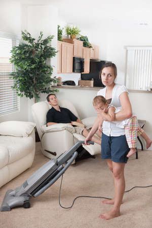 A mother trying to vacuum while the father sits around Stockfoto