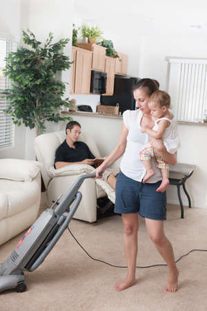 caucasian ancestry: A mother trying to vacuum while the father sits around Stock Photo