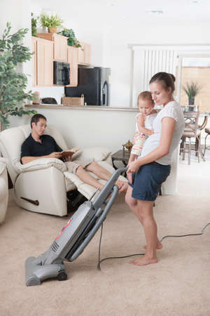 A mother trying to vacuum while the father sits around Stock Photo