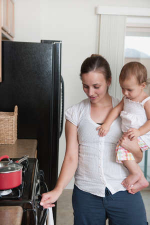 A mother cooking and holding a baby photo