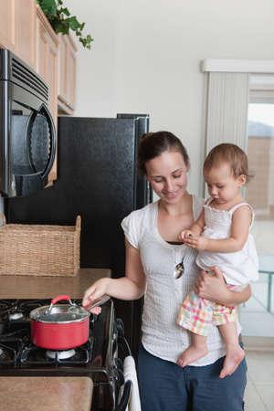 mere cuisine: Une m�re cuisine et tenant un b�b�  Banque d'images