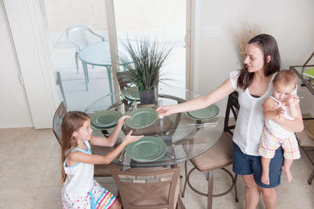 baby cutlery: A mother and daughter setting the table together