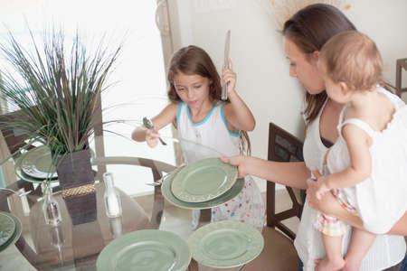 enfant banc: Une m�re et la fille de mettre la table ensemble