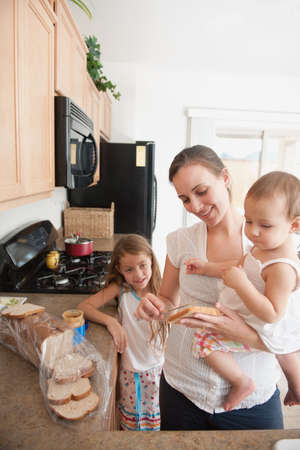 caucasian ancestry: A mother making a sandwich for his girls Stock Photo