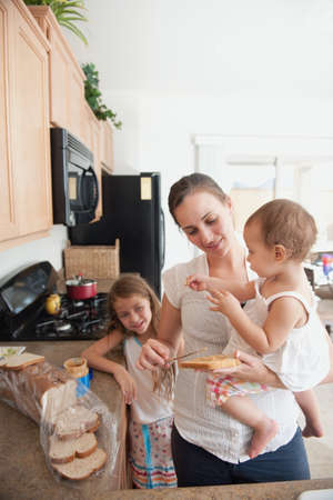 A mother making a sandwich for his girls photo