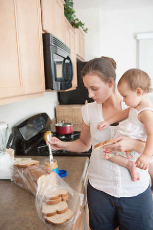 A mother making a sandwich for his baby girl photo