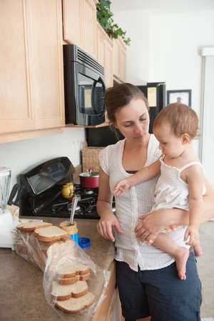 caucasian ancestry: A mother making a sandwich for his baby girl