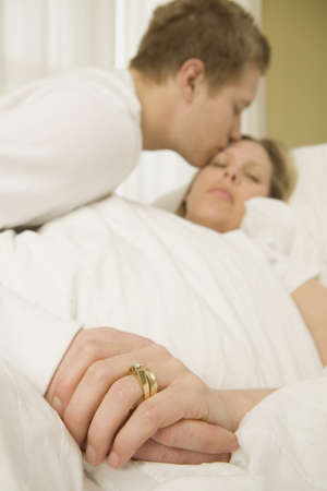 sick day: Loving husband caring for sick wife in bed
