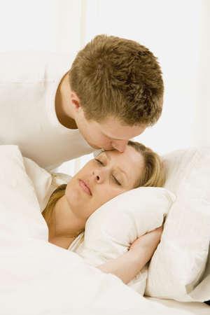 esposas: Amoroso marido cuidando enferma esposa en la cama