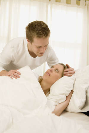 Husband caring for wife who is in bed sick photo