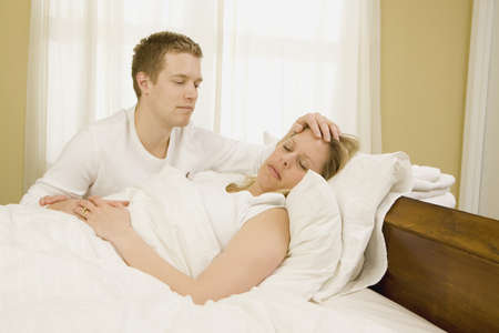 caucasian ancestry: Loving husband caring for sick wife in bed