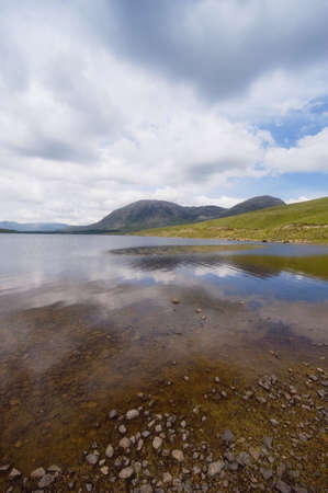 shallow water: The sky reflected in shallow water with mountains in the background
