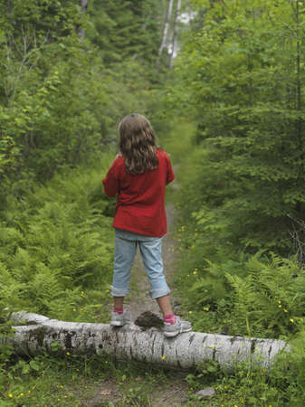 Young girl standing on log, Lake of the Woods, Ontario, Canada Stock Photo