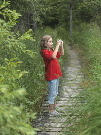 caucasian ancestry: Young girl on pathway taking a picture, Lake of the Woods, Ontario, Canada