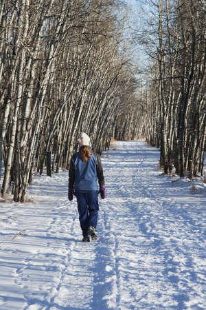 winter woman: Woman walking on pathway in the winter