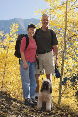 40s adult: Couple hiking with a dog in a mountains in the autumn