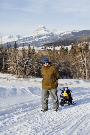 Father pulling son on sled in the winter photo