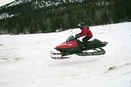 caucasian ancestry: Snowmobile in the air Stock Photo